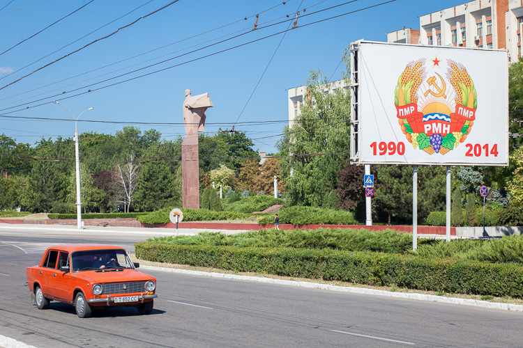 An old Russian Lada passes an anniversary sign of the Soviet state in Tiraspol