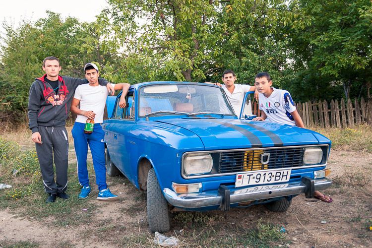 Local kids are hanging out around a Moskvich car