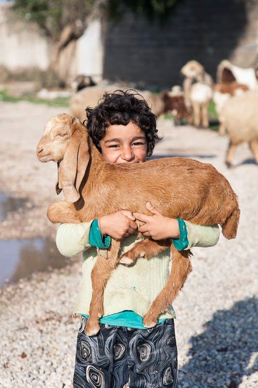 A girl proudly showing off one of her goats