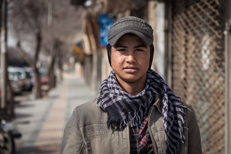 An Afghan refugee poses in front of my camera on the streets of Yazd