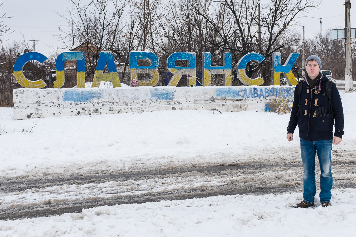 Standing at the scarred sign of Slavyansk city. It was painted in national colors after the separatists had left.