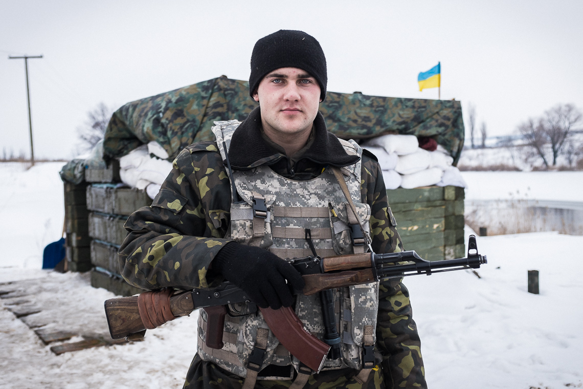 A Ukrainian soldier is guarding at a checkpoint
