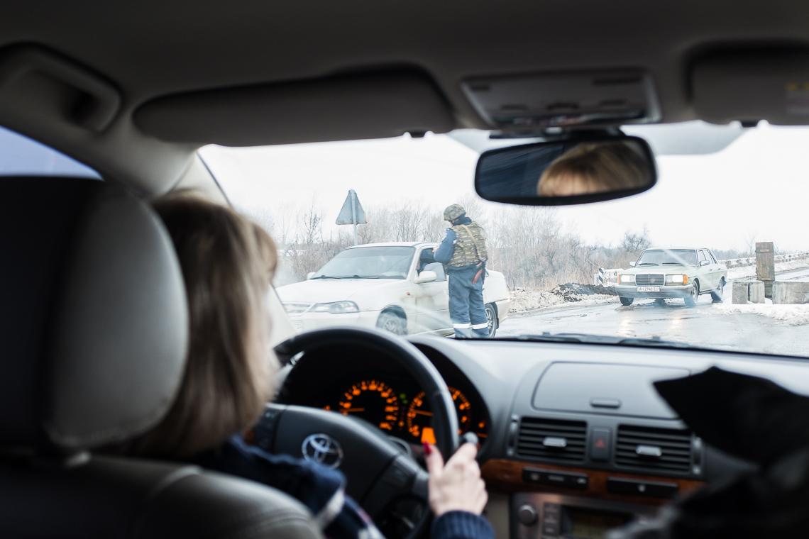 A Ukrainian soldier checks a car at a checkpoint