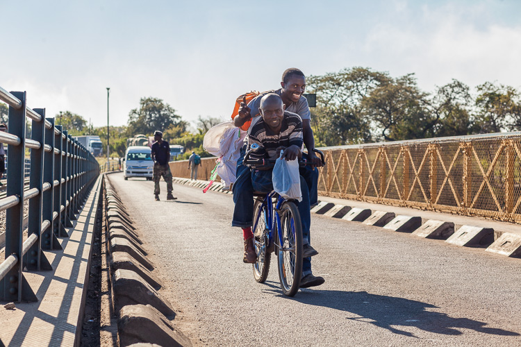 Two young boys working between the two borders, driving their bike across the Victoria Falls bridge