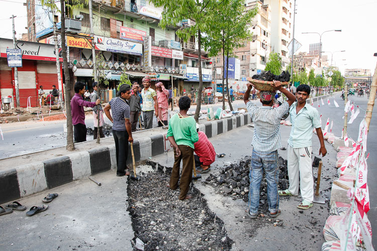 In Dhaka you run into the most astonishing scenes, like these 12 workers hammering down on the bitumen