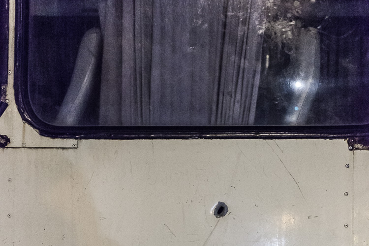 Another bullet hole in a bus parked at Junta. The driver told me the woman in the seat had died.