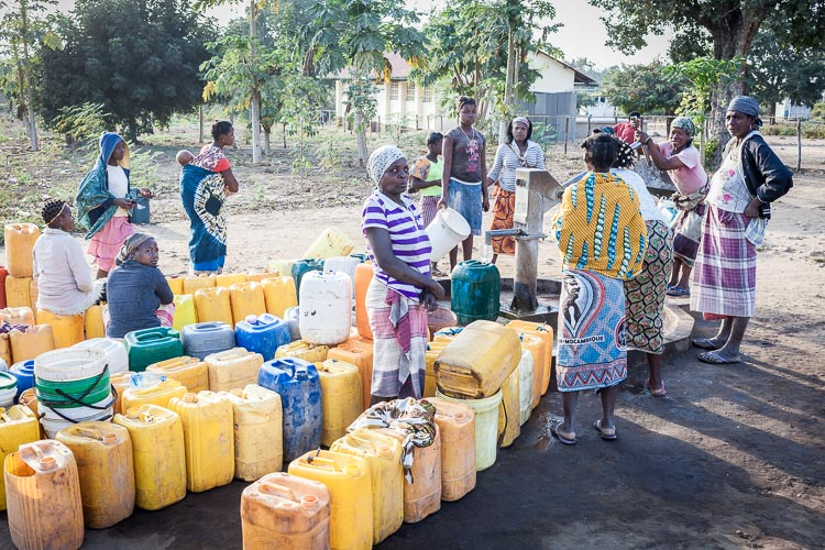 Early morning, women are collecting water from a well in Save