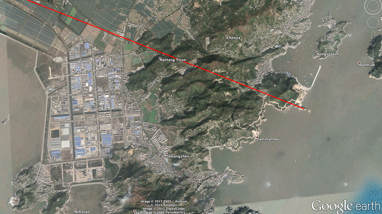 The location in China where the route touches the Pacific Ocean, in the middle of an industrial area