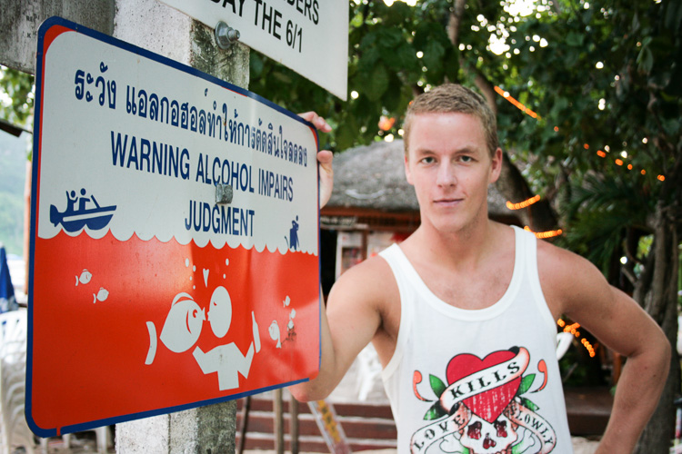 Me, posing at a sign that warns foreigners against alcohol abuse on the Thai island of Ko Phi Phi