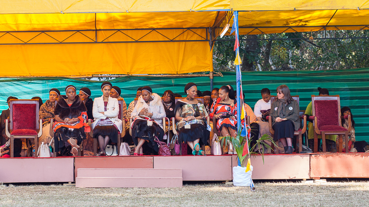 Mswati III's 16 wives, sitting on a separate stage next to the King