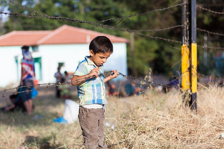 A young boy near the Idomeni train station looks at a piece of barbed wire. While travelling the Balkan route towards the EU, he will often be confronted with similar defenses.