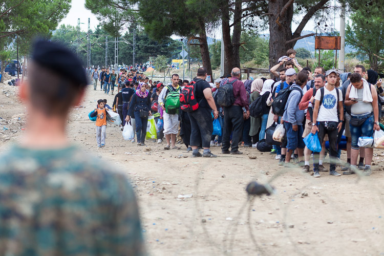 A Macedonian soldier overlooks a group of refugees as they are about to cross the border from Greece.