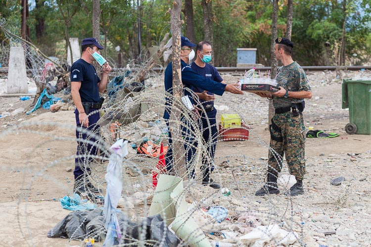 Greek police step into Macedonian territory, handing out cold drinks to the Macedonian army. Much of the order at the border is a direct result of the level of their cooperation, which remains good until today