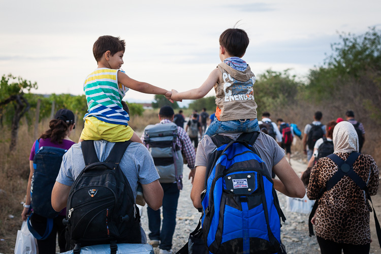 Two young Syrian boys ride on top of their fathers' shoulders after just having left Greece. For many children, the journey towards the EU seems more of an adventure because they are to young to realise the situation.