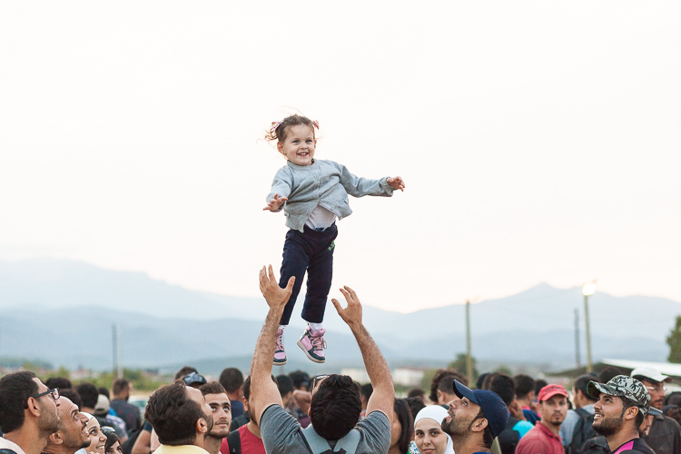 A young girl is lifted up in the air while the crowd waits to enter the Gevgelija camp in south Macedonia.