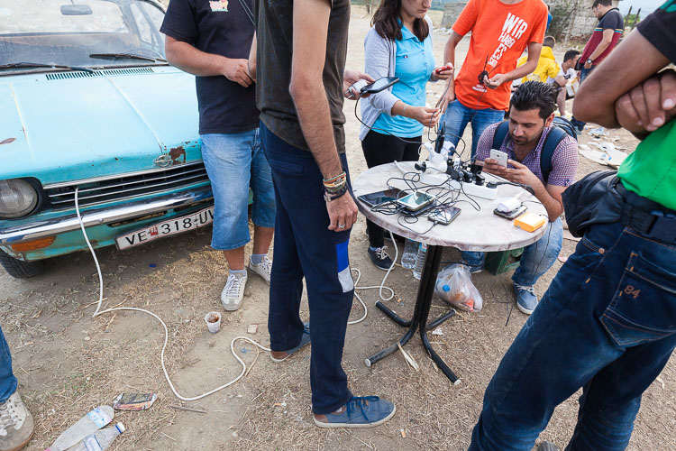 Locals have created a small recharging station from an old Opel. Refugees need to pay up to €2 per phone.
