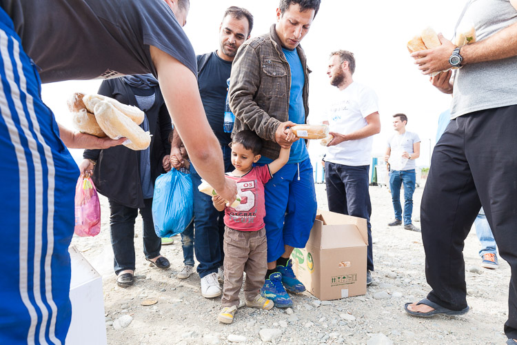 A young Syrian boy receives a sandwich from a local volunteer as he enters the Gevgelija refugee transit camp.
