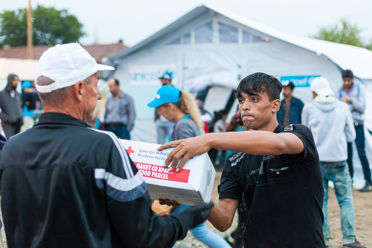 A refugee helps out resupplying a Red Cross barrack in the Gevgelija refugee camp. Often, refugees are bored and need to find ways to entertain themselves while waiting for documents or transportation. Most of them are also extremely thankful for the help they receive from volunteers along the Balkan route.