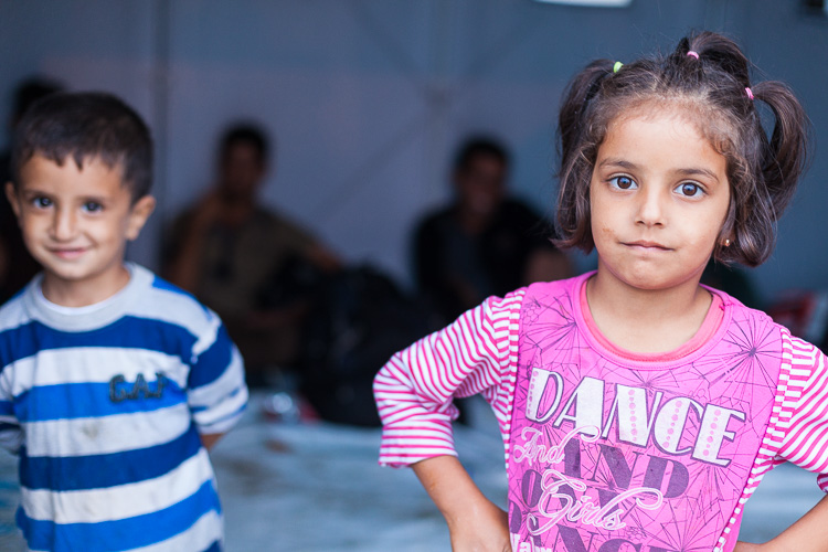 Two Syrian children play around in a UNHCR barrack before they are boarding a train to Tabanovce.