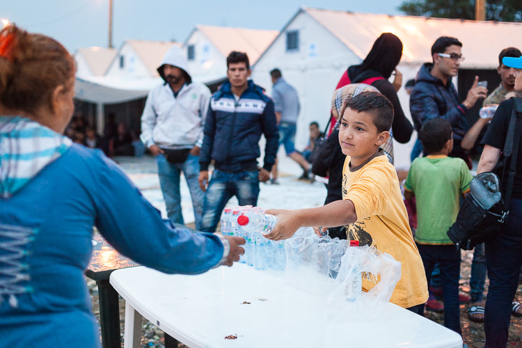 A young (refugee) boy hands out water to other refugees inside the Gevgelija refugee camp.