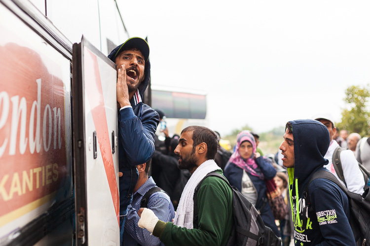 A man screams to his friends while getting on a bus during a day of railway strike.