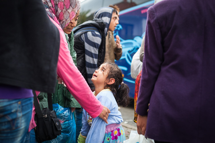 A young girl cries as a small chaos errupts when people try to get on buses that will take to the border with Serbia.