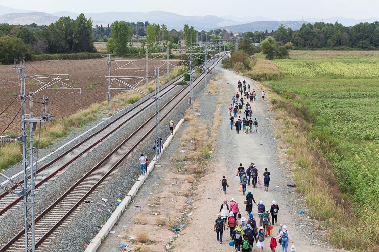 A group of refugees walk along the railway with only 5 kilomters left on their way to the border Greece-Macedonia