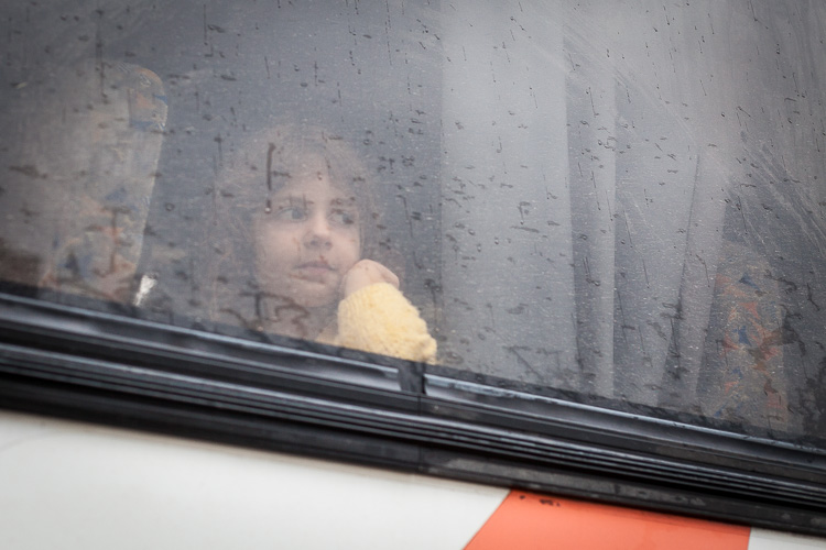 A young girls stares out the window of a bus, as it is pouring down outside the Gevgelija refugee camp.