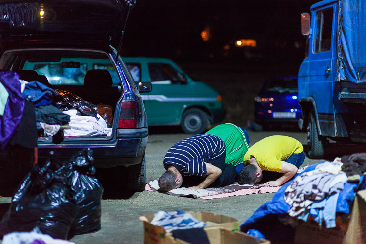 Albanian Macedonian volunteers pray at the Tabanovce train station. They are there every day during the night, donating food and clothes to predominantly Muslim refugees.