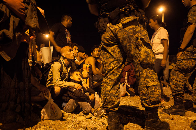 A child and his father sit down as they obey orders given to them by Macedonian soldiers, before boarding a night train towards Tabanovce.