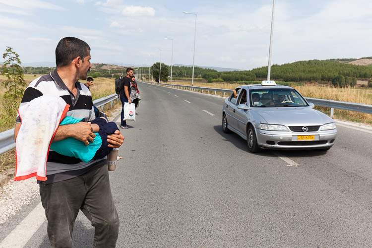 A father in distress, carrying his disabled child while attempting to take a taxi on his way to Idomeni, Greece