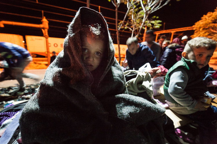 A child, wrapped up warmly by volunteers, cries for his mother at 3AM after arriving in Tabanovce.