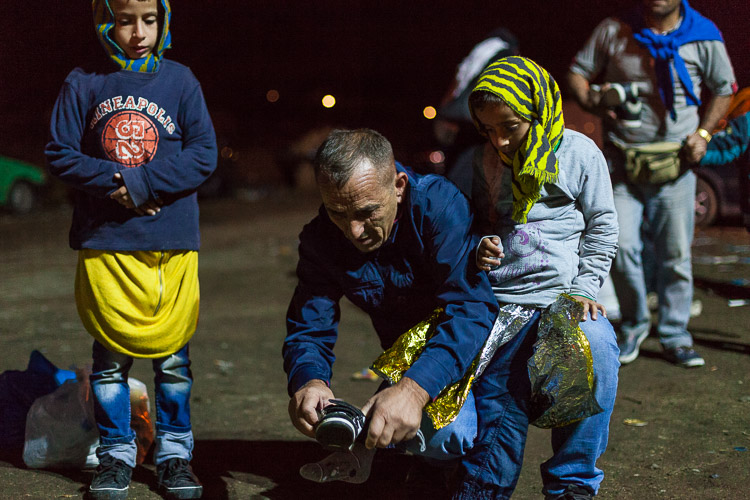 As children are arriving near the Macedonia-Serbia border at Tabanovce, volunteers from the town Studenichani fit new shoes, socks and clothes to the children. They are often freezing, wet and scared, arriving in the mid of night from the refugee camp in Gevgelija