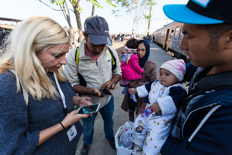 A Macedonian volunteers explains to some Afghan refugees how to travel into the EU through Croatia as news poored in that Hungary had sealed off its borders.