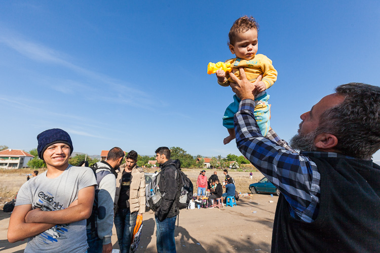 An Albanian Macedonian Imam lifts up a child on an early morning in Tabanovce train station. The love the refugees receive from local volunteers is unconditional.