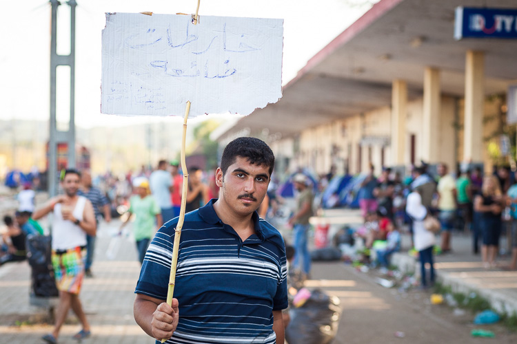 """A man is walking around the train station of Idomeni, holding a sign that assumedly says """"Death to Assad"""""""