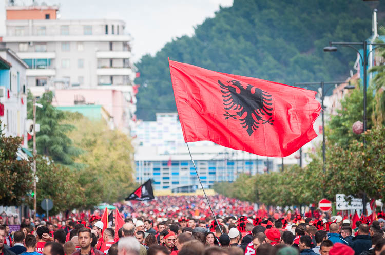 A large Albanian flag, depicting a double headed eagle, is carried towards the Elbasan Arena