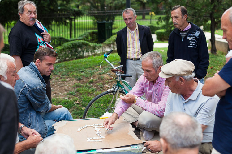 A group of old men are playing several rounds of dominos in a park downtown.