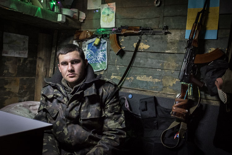 A Ukrainian soldier sits inside a heated barrack, which is set up next to a blown-up bridge on the outskirts of Sloviansk in east Ukraine.