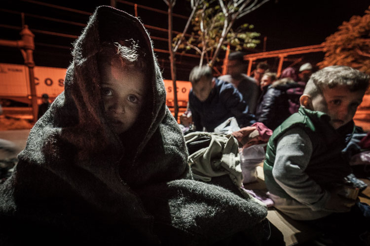 A child, wrapped up warmly by volunteers, cries for his mother at 3AM after arriving in Tabanovce, north Macedonia..