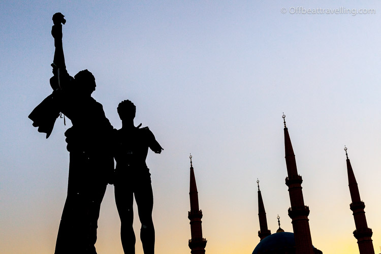 Martyrs' Monument in downtown Beirut with the Blue Mosque in the background. The statue was damaged in the 1975-1990 civil war, which can still be seen today.